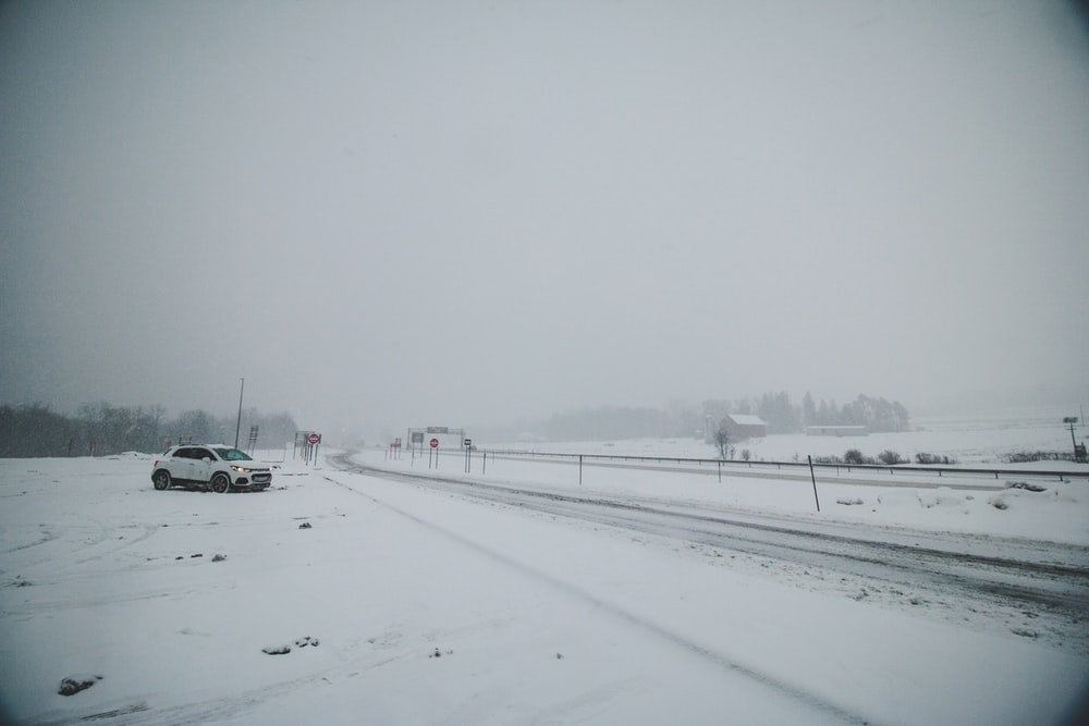 white car on snow covered road during daytime