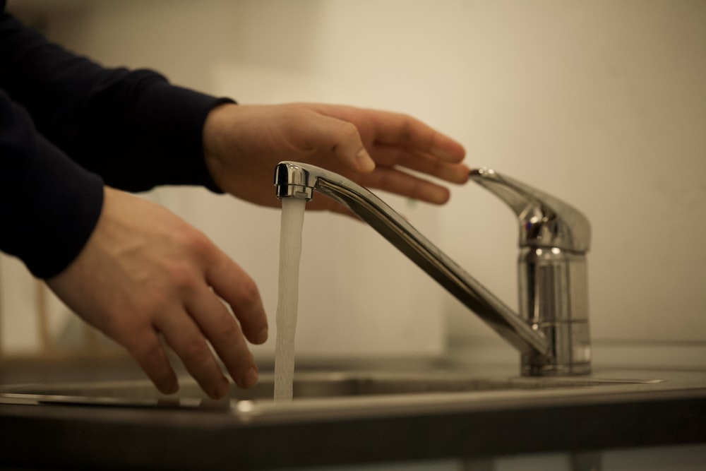 person in black long sleeve shirt holding stainless steel faucet