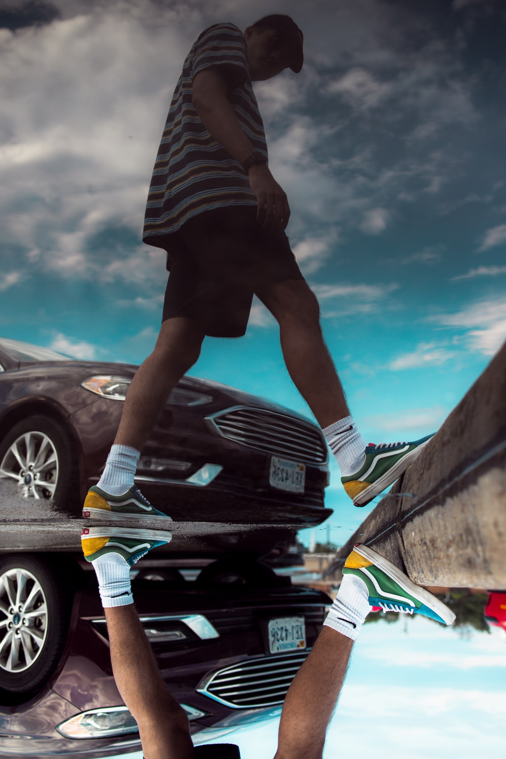 man in black shorts and white sneakers standing on black car