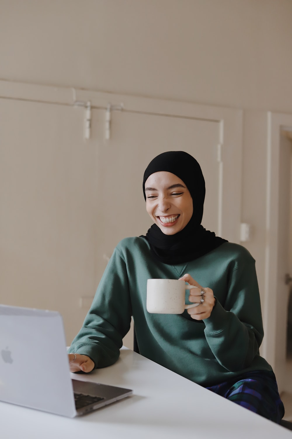 woman in green hijab holding white ceramic mug