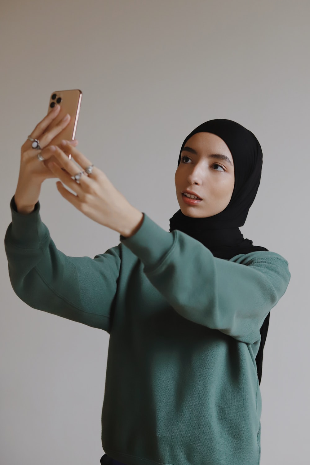 woman in green long sleeved shirt holding silver iphone 6