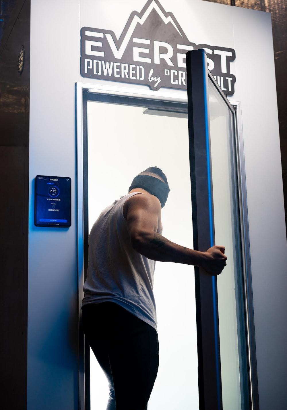 man in gray crew neck t-shirt and black pants standing beside blue door