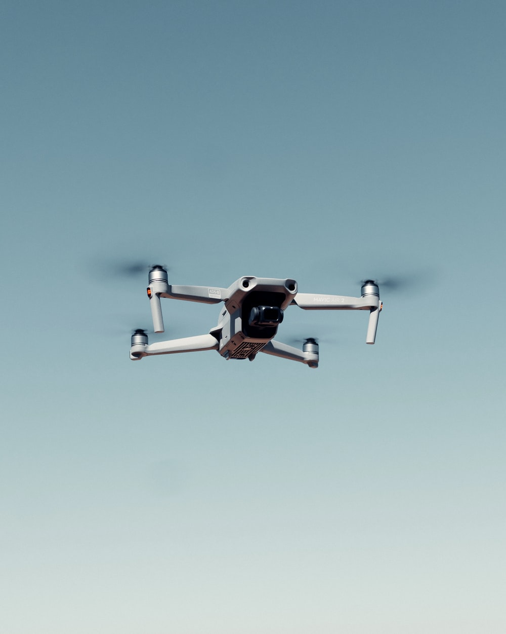 black and white drone flying under blue sky during daytime