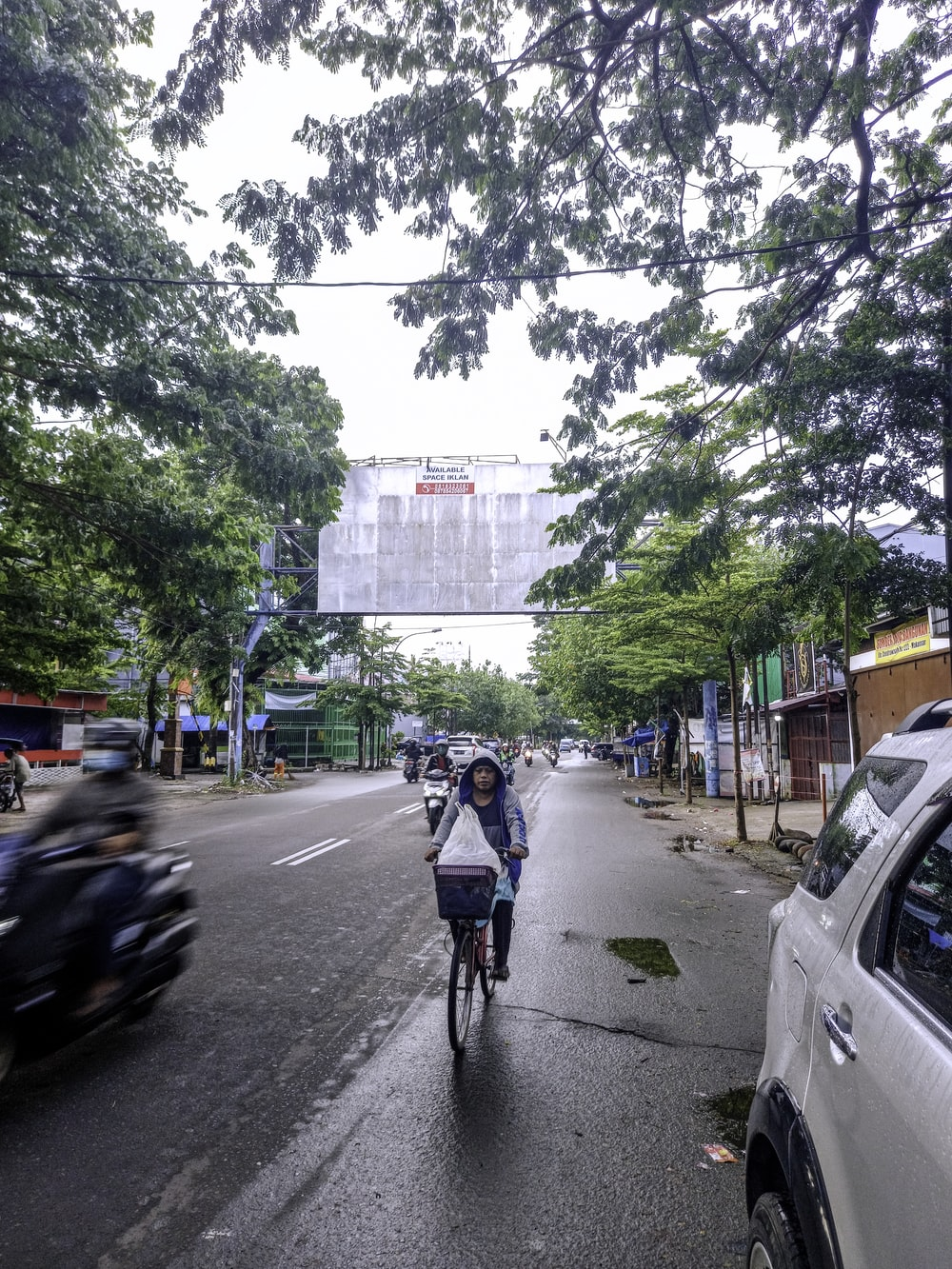 woman in blue jacket riding bicycle on road during daytime
