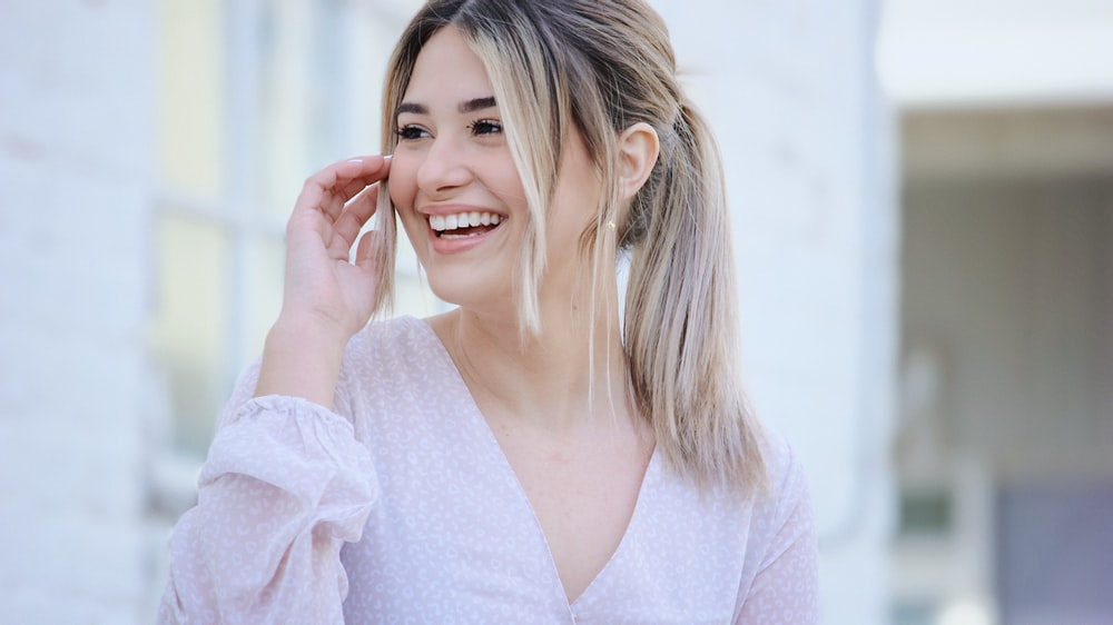 woman in white v neck long sleeve shirt smiling