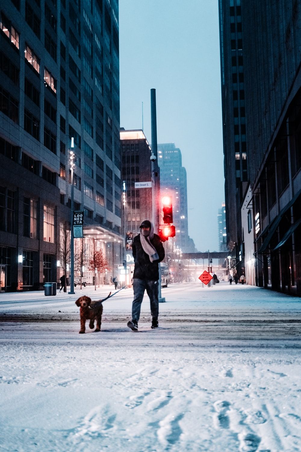 person in black jacket and blue denim jeans walking on snow covered road during daytime
