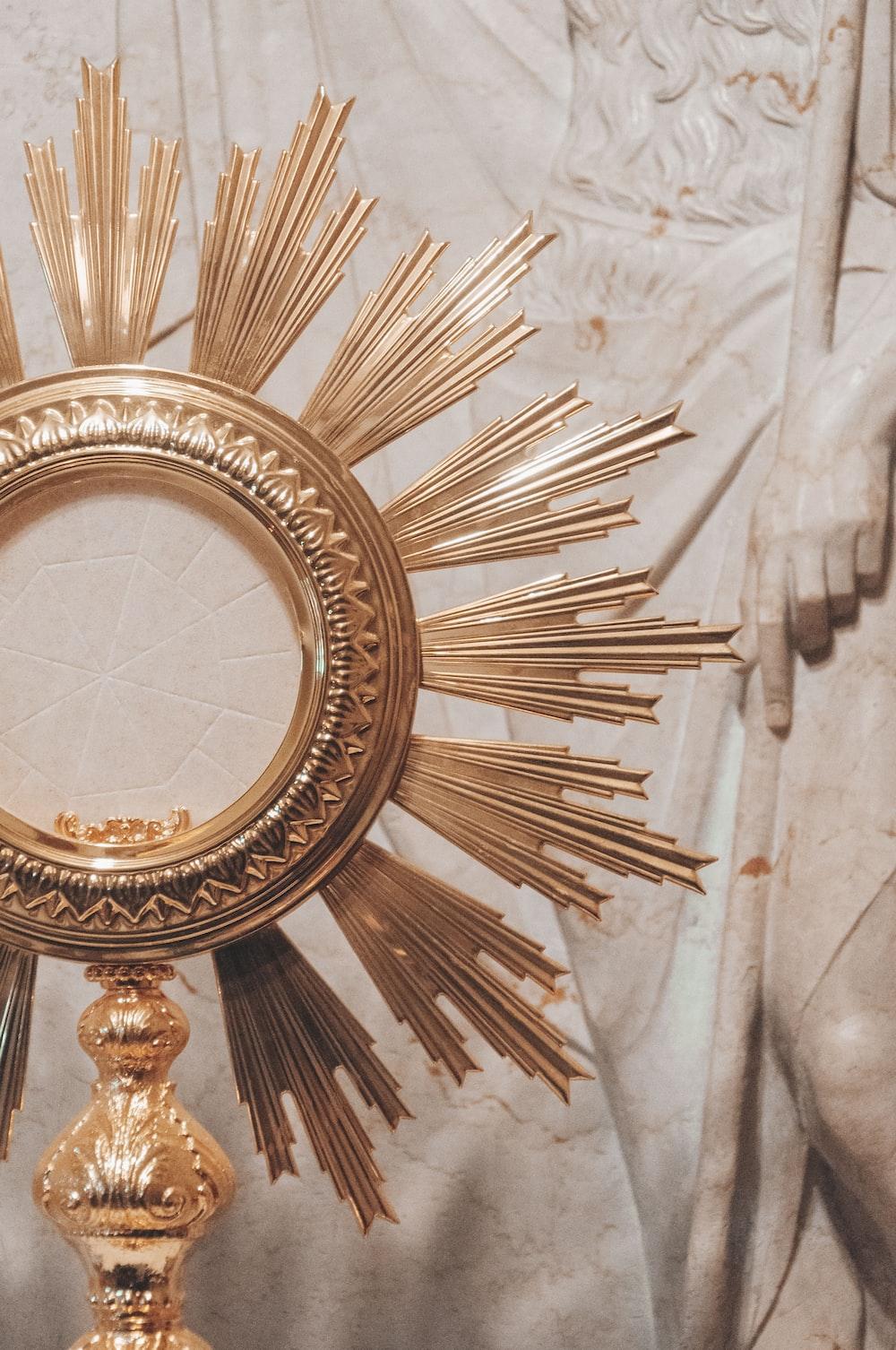 gold round framed mirror on white textile