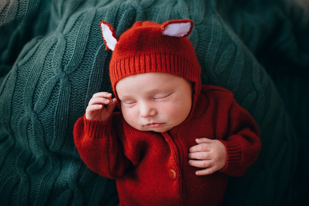 baby in red knit cap and red button up jacket