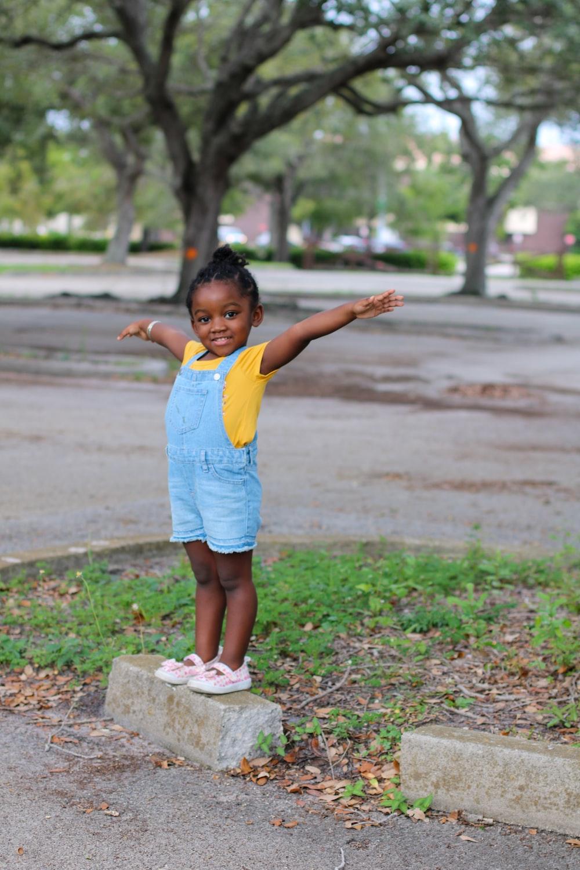 girl in yellow shirt standing on gray concrete blocks during daytime