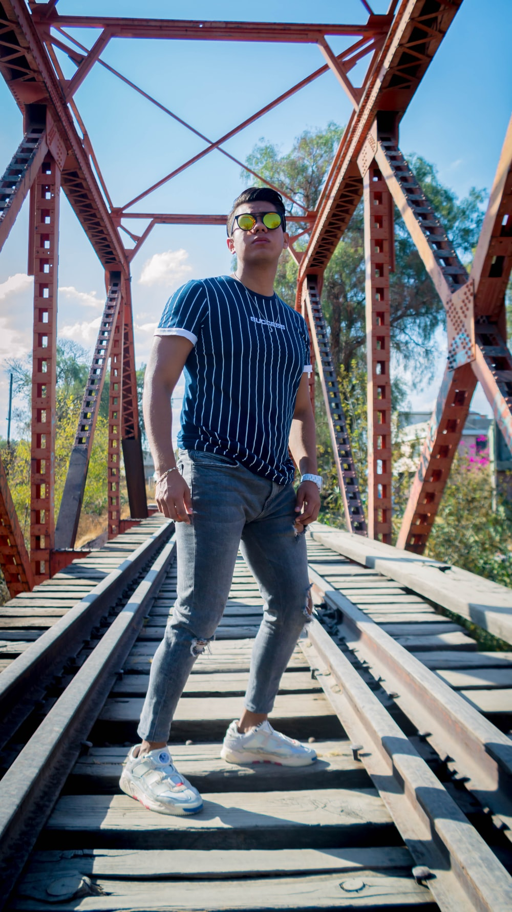 man in blue and white stripe polo shirt and blue denim jeans standing on brown wooden