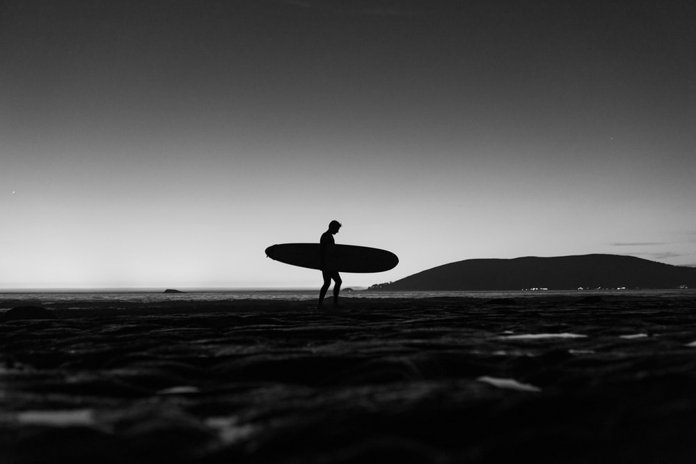 silhouette of man holding surfboard walking on beach