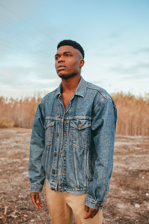man in blue denim jacket standing on brown field during daytime