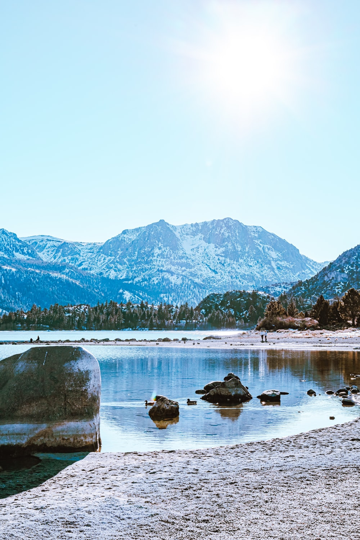 lake near mountain under white sky during daytime