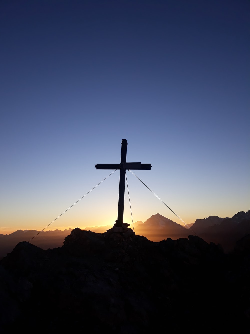 silhouette of cross on rock formation during sunset