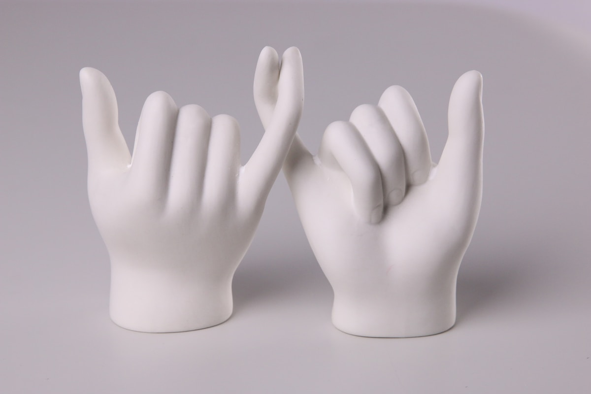 Sculpture of two white hands on a grey background making a pinky promise