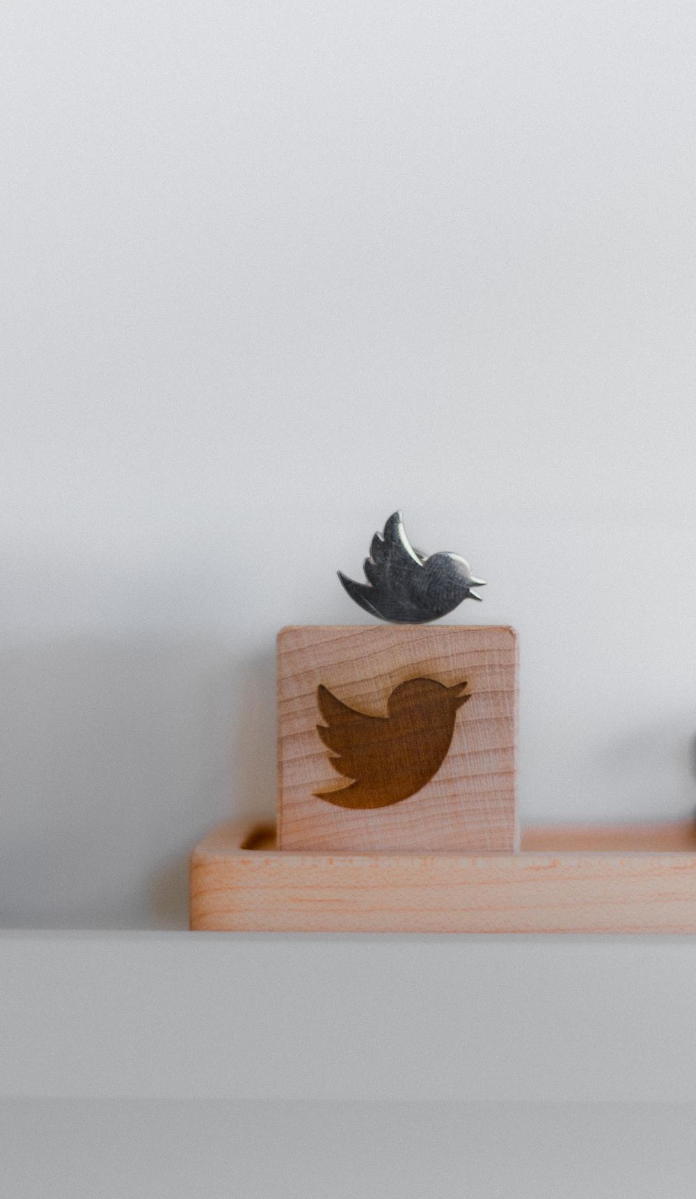 brown wooden bird house on brown wooden box