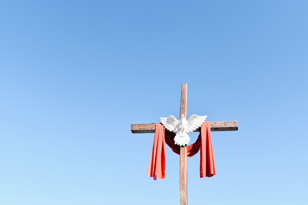 brown wooden cross with red and white ribbon