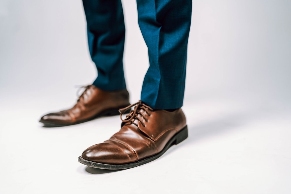 person in blue pants and black leather shoes