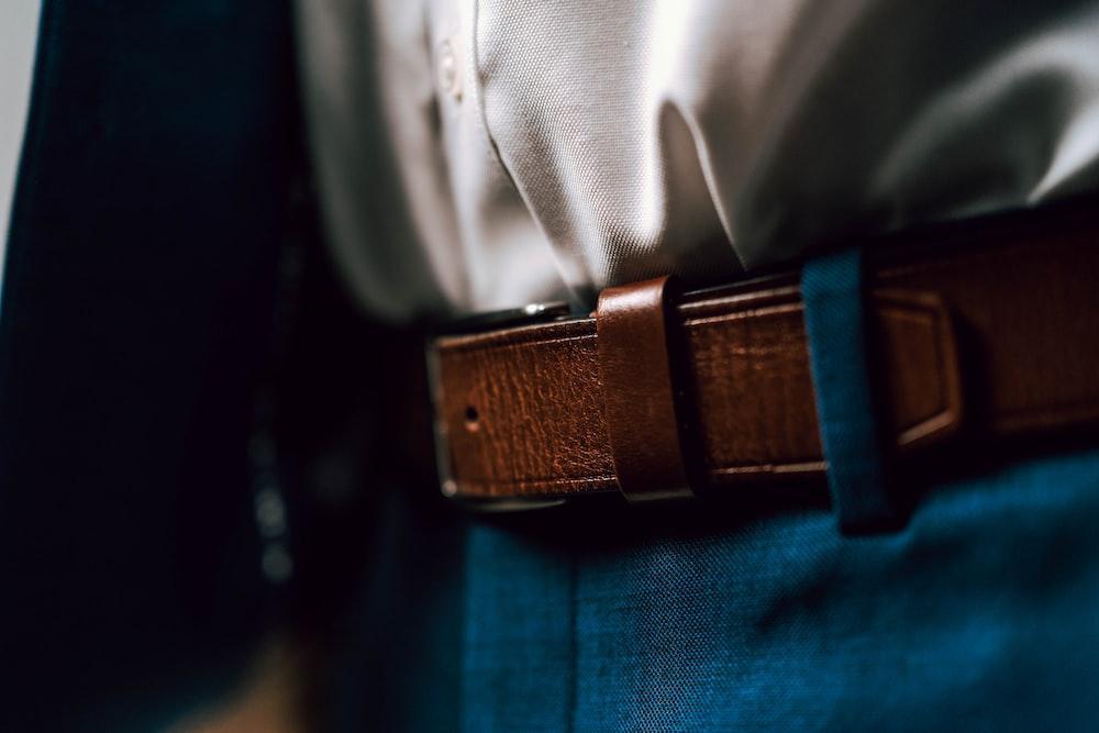 black leather belt on blue denim jeans