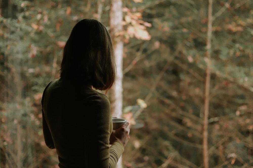 woman in brown long sleeve shirt holding white ceramic mug