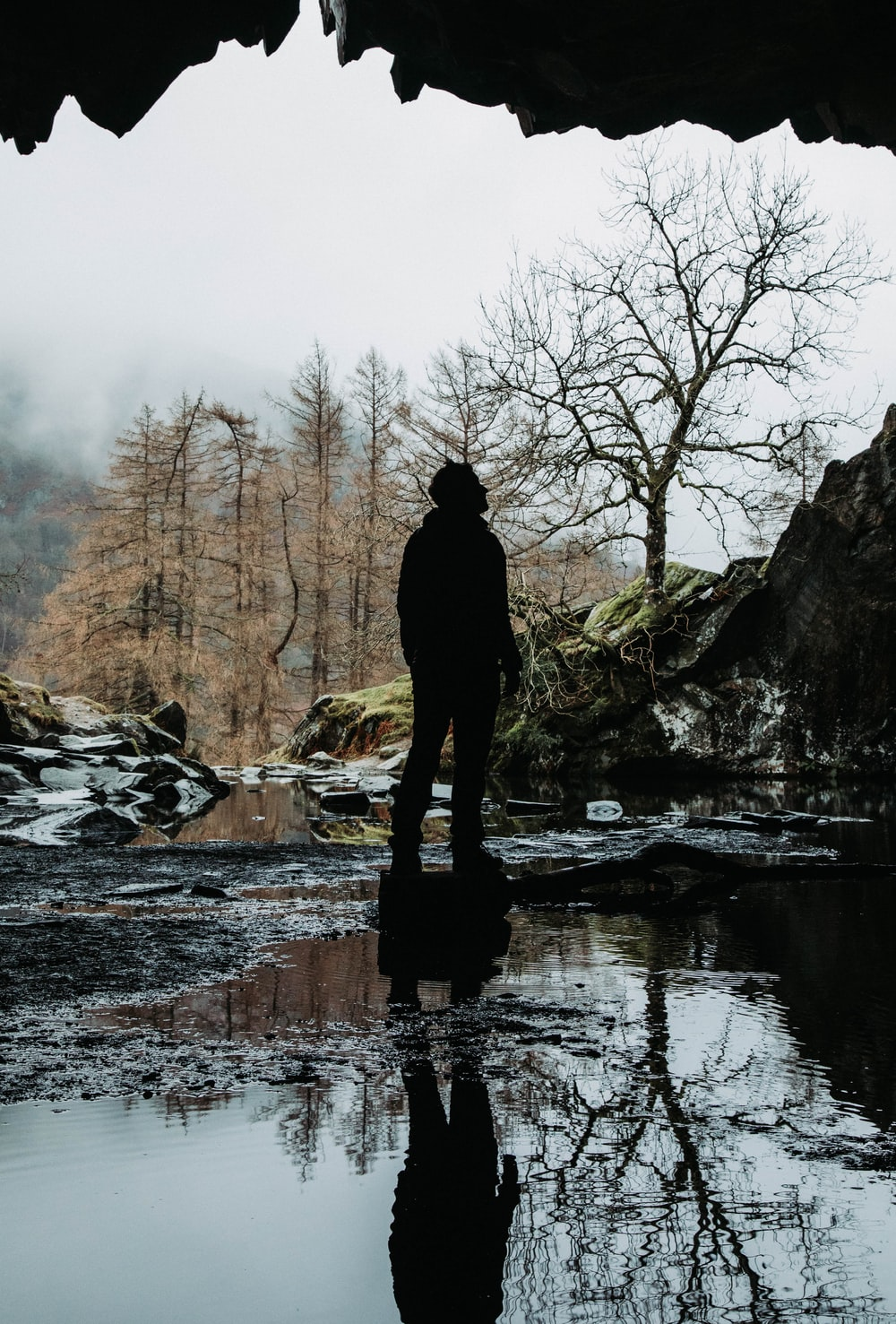 person standing on rock in river