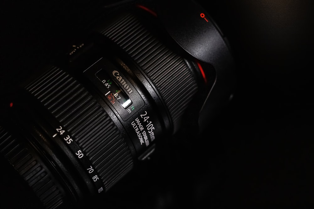 black canon camera lens on black surface