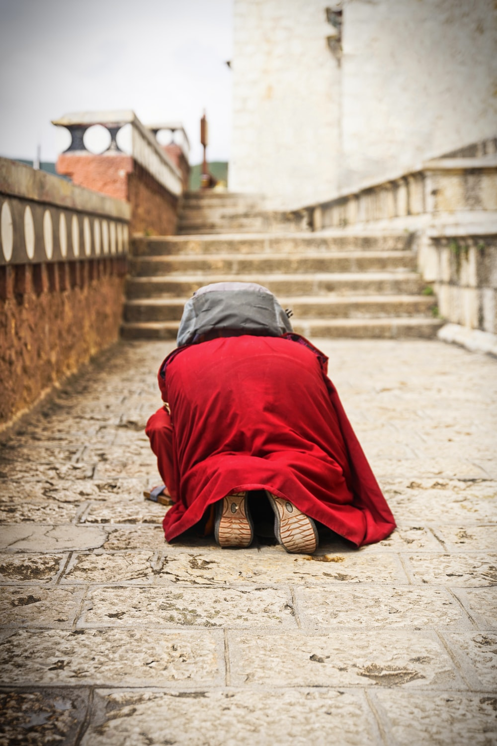 person in red and black robe sitting on brown concrete stairs