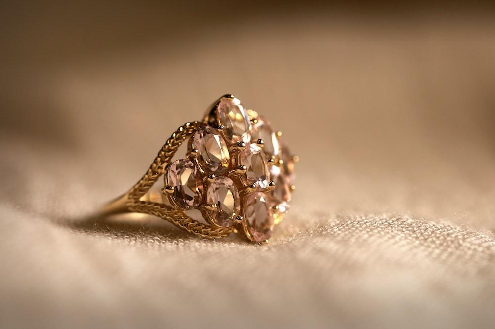 gold diamond studded ring on white textile