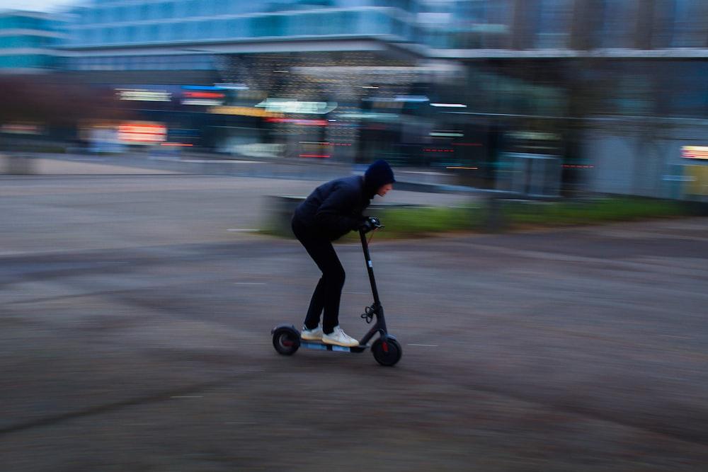 man in black jacket riding black kick scooter on road during daytime
