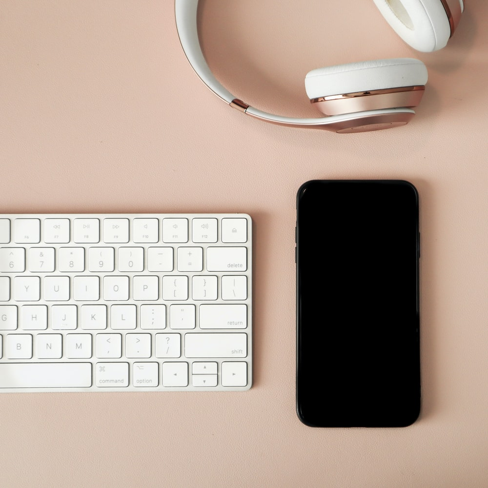 black iphone 7 beside white apple keyboard and white wireless computer mouse