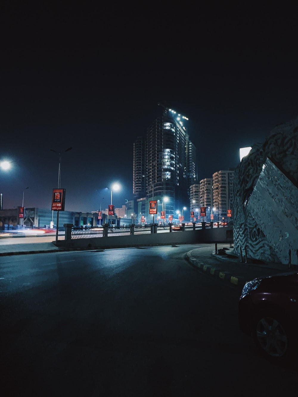 cars on road near city buildings during night time