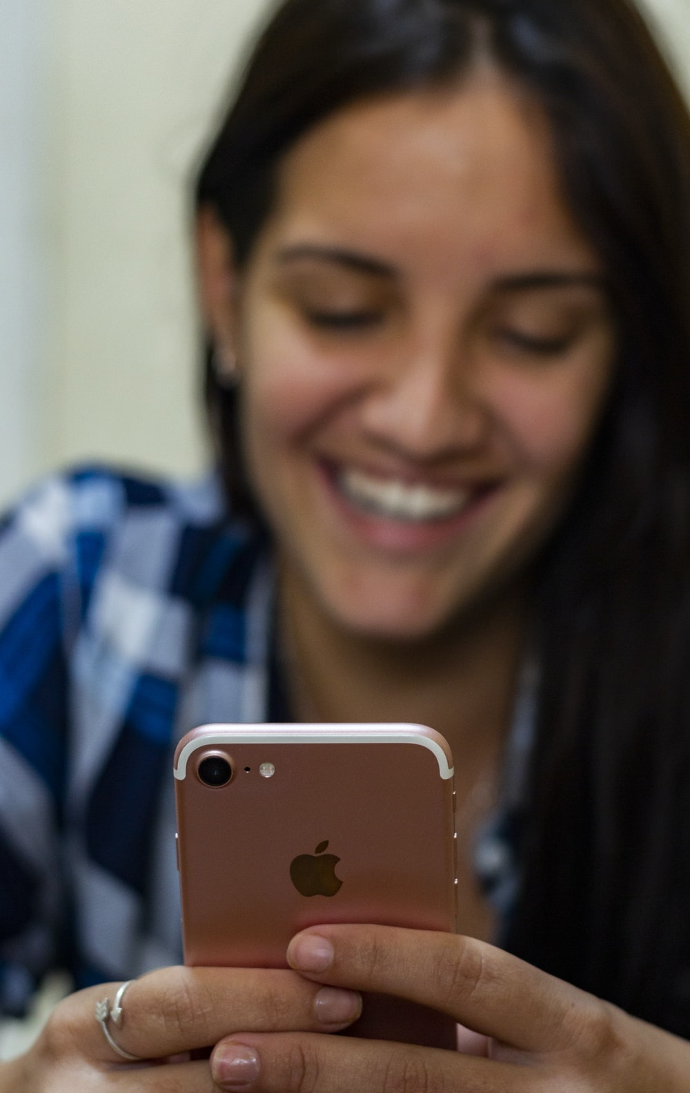 woman in blue and white plaid shirt holding gold iphone 6
