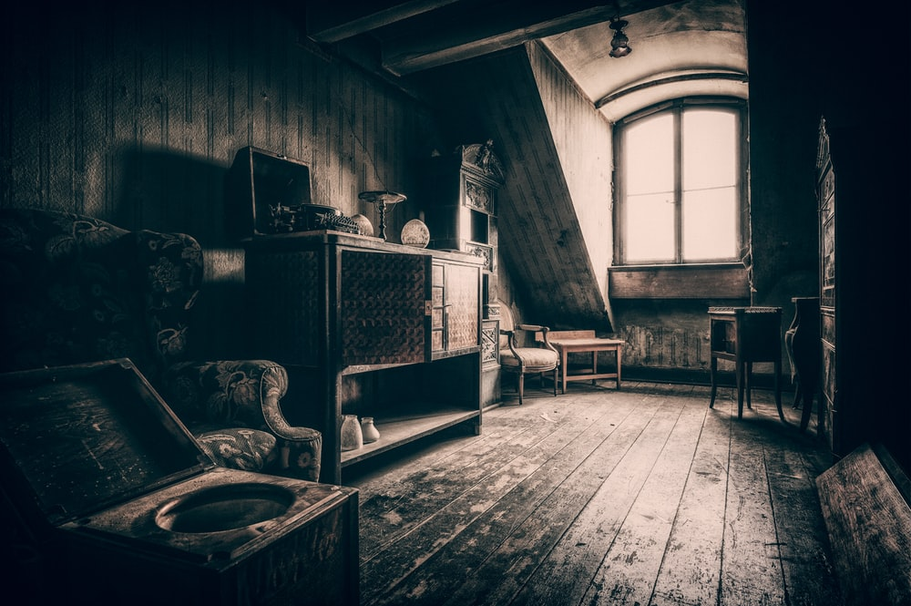 grayscale photo of wooden chair near window