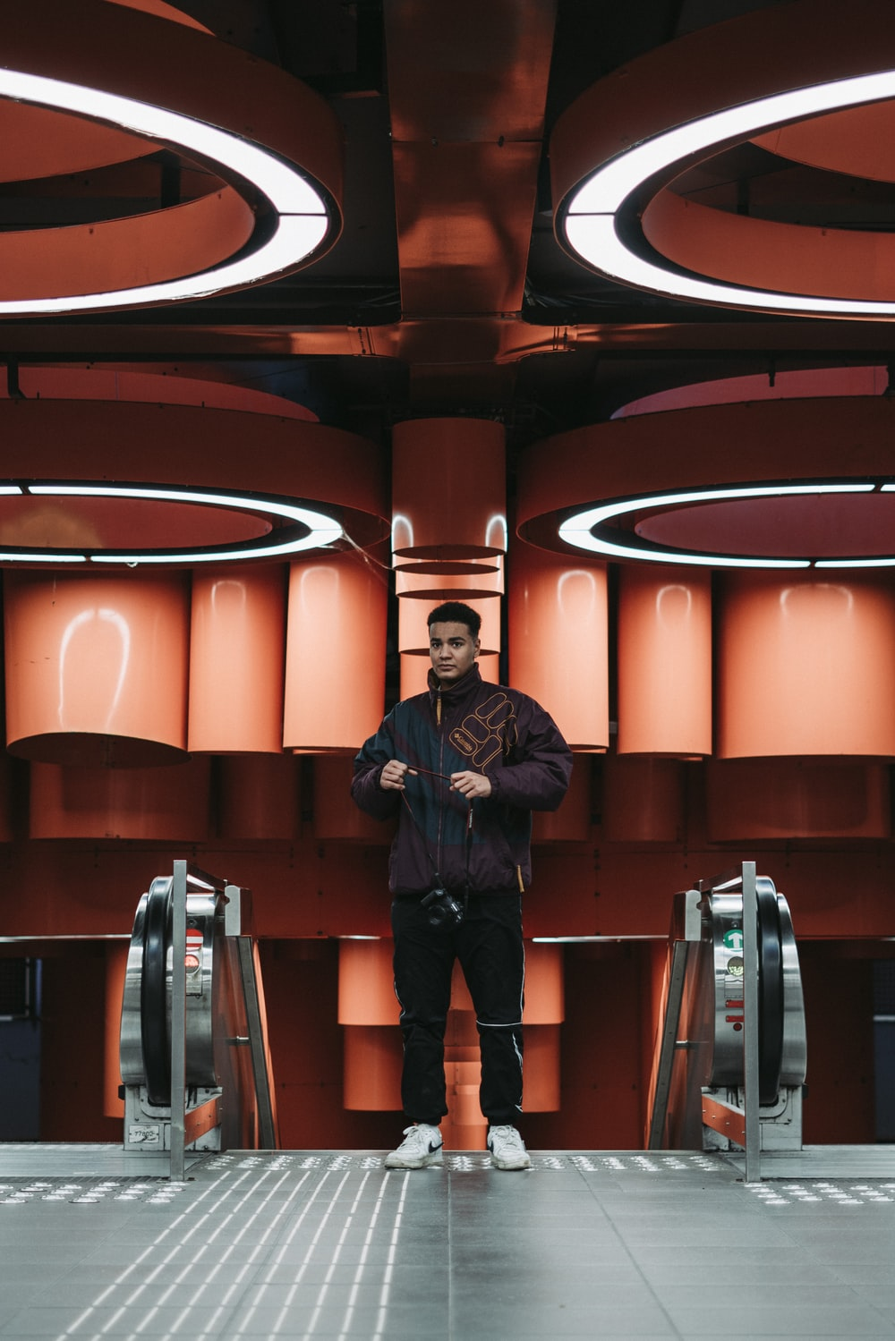 man in black jacket standing on escalator