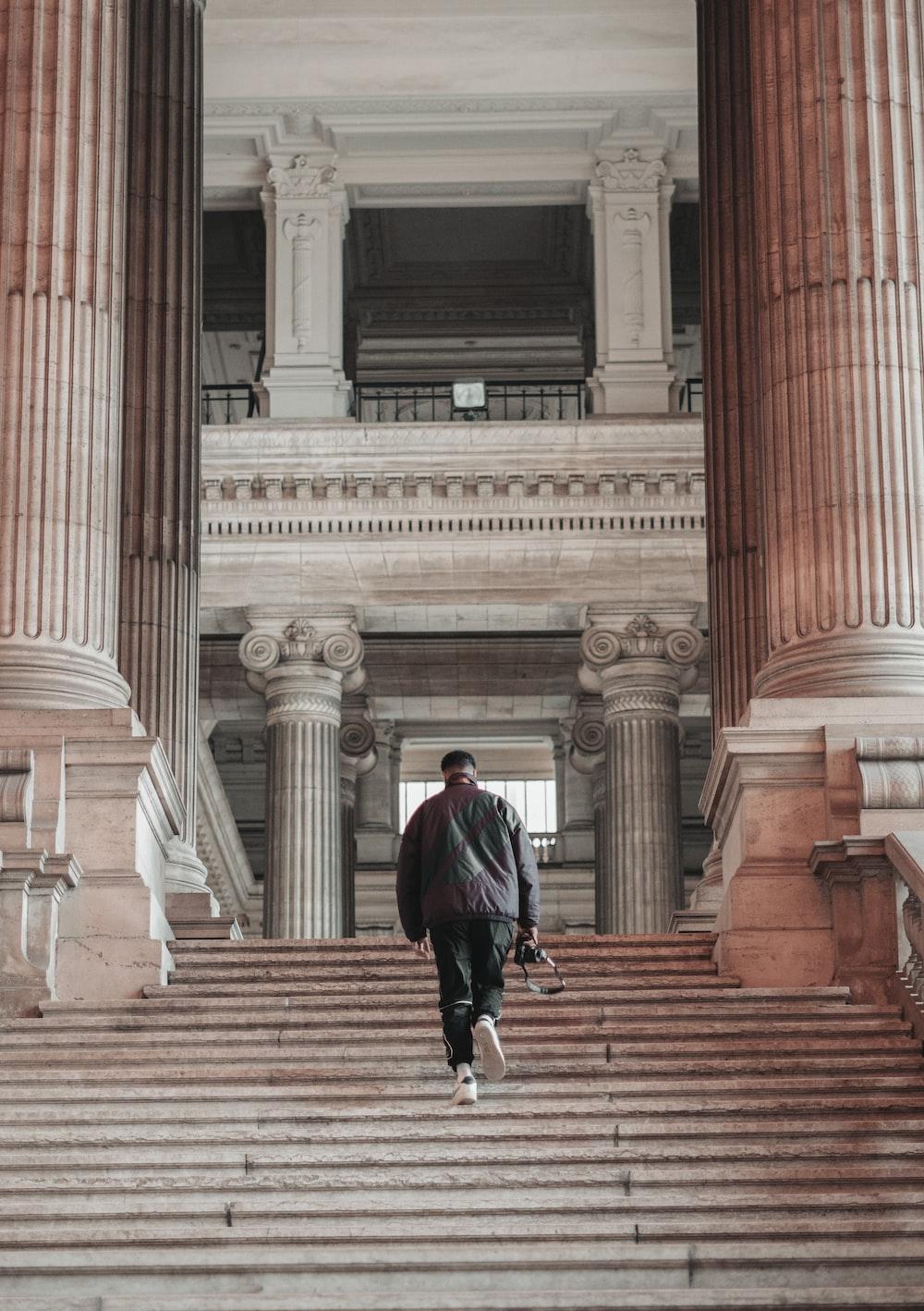 woman in black jacket walking on brown concrete stairs