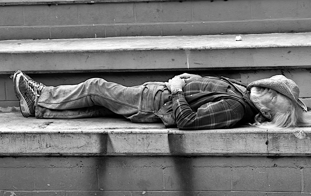 grayscale photo of man in pants and jacket sitting on concrete stairs
