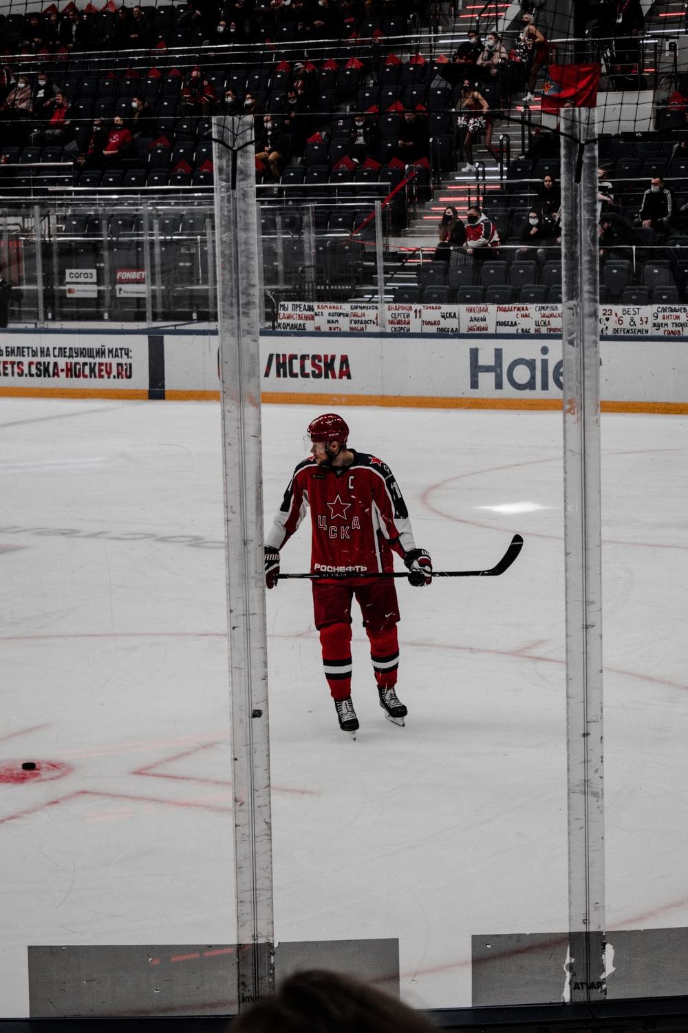 man in red ice hockey jersey playing ice hockey
