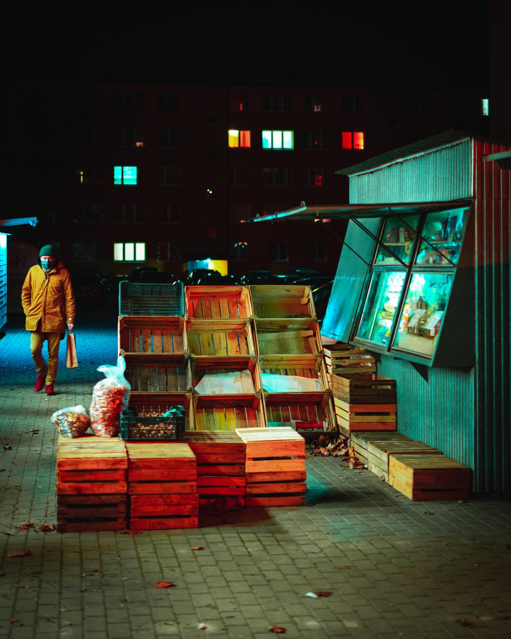 man in blue t-shirt standing beside brown wooden boxes