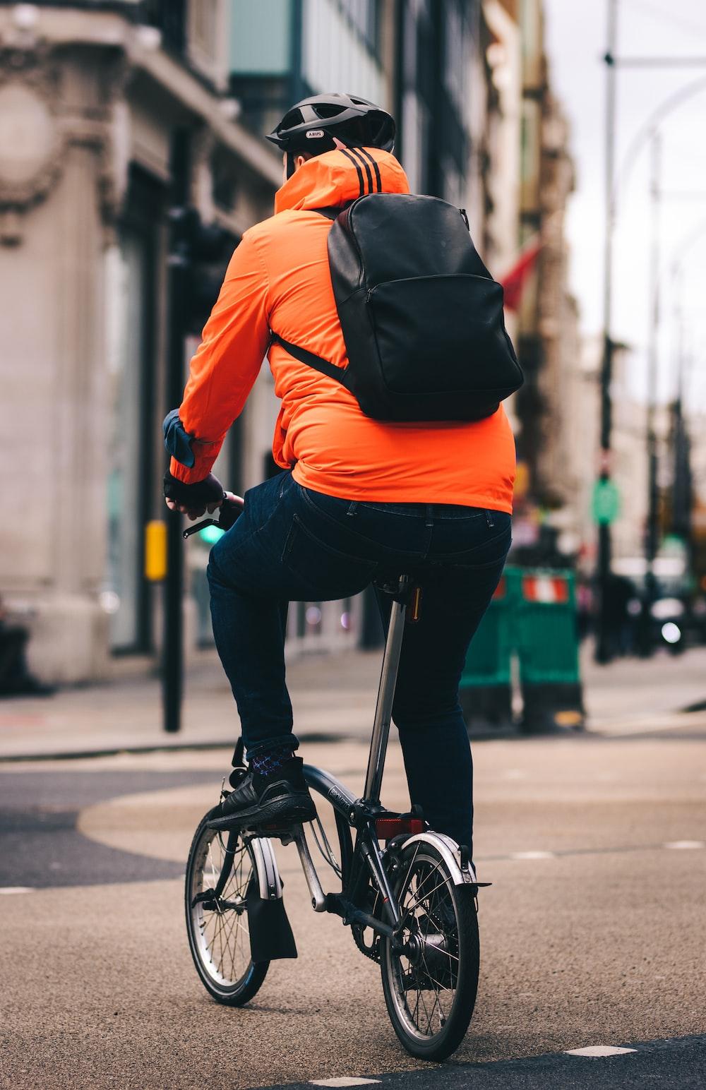 man in orange jacket riding bicycle during daytime
