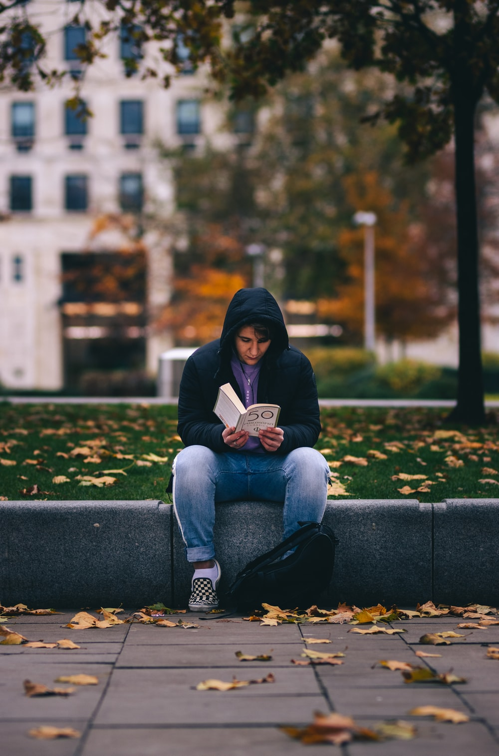 woman in blue denim jeans reading book sitting on blue concrete bench during daytime