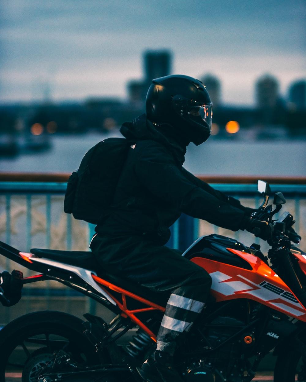 man in black jacket riding orange and black motorcycle