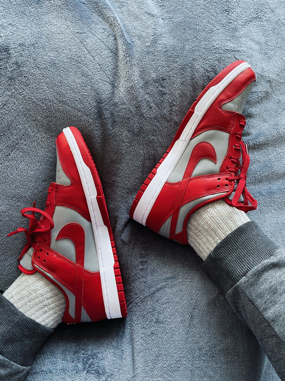 person wearing red and white nike sneakers