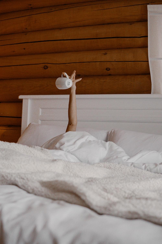 white bed linen near brown wooden headboard