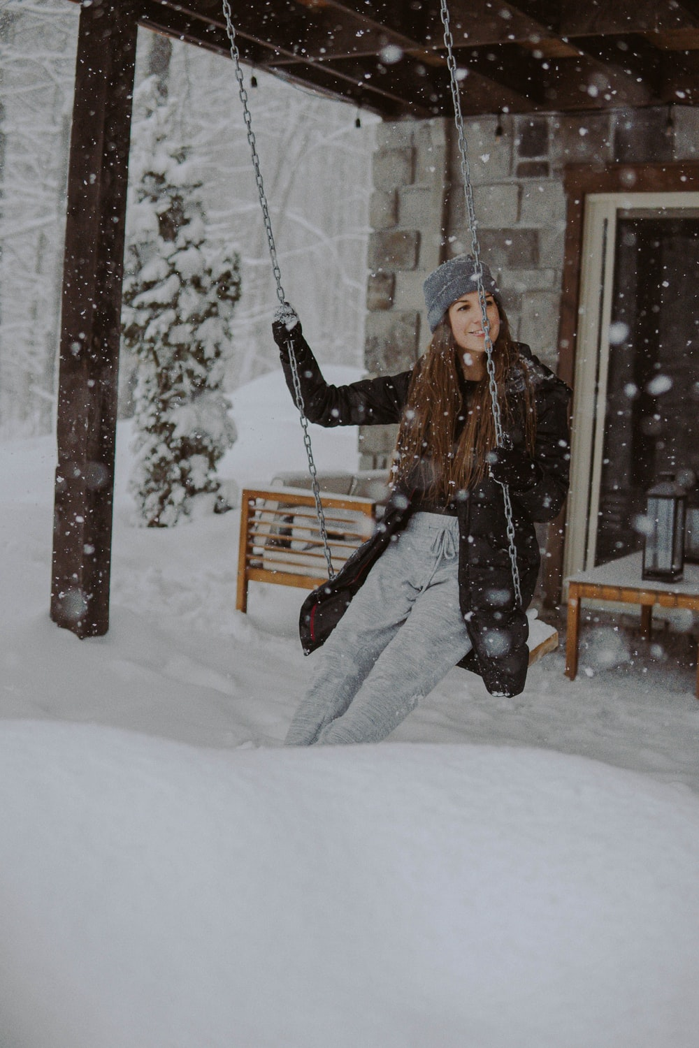 woman in black jacket and black pants sitting on brown wooden swing covered with snow
