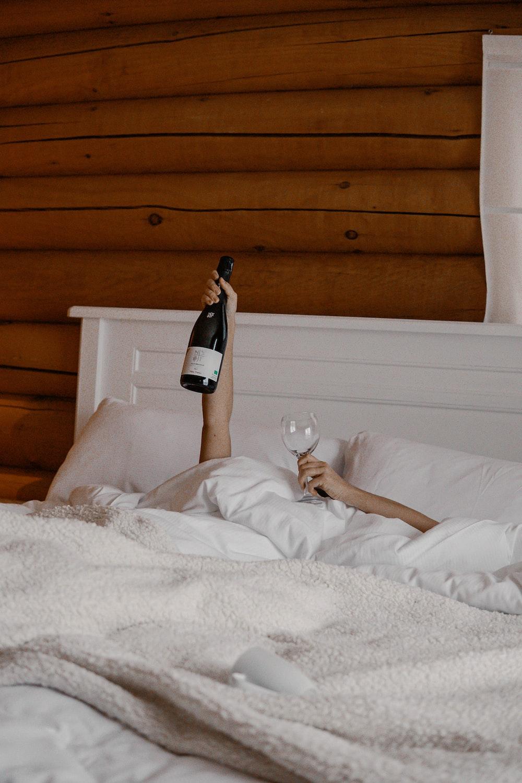woman in white dress holding wine bottle