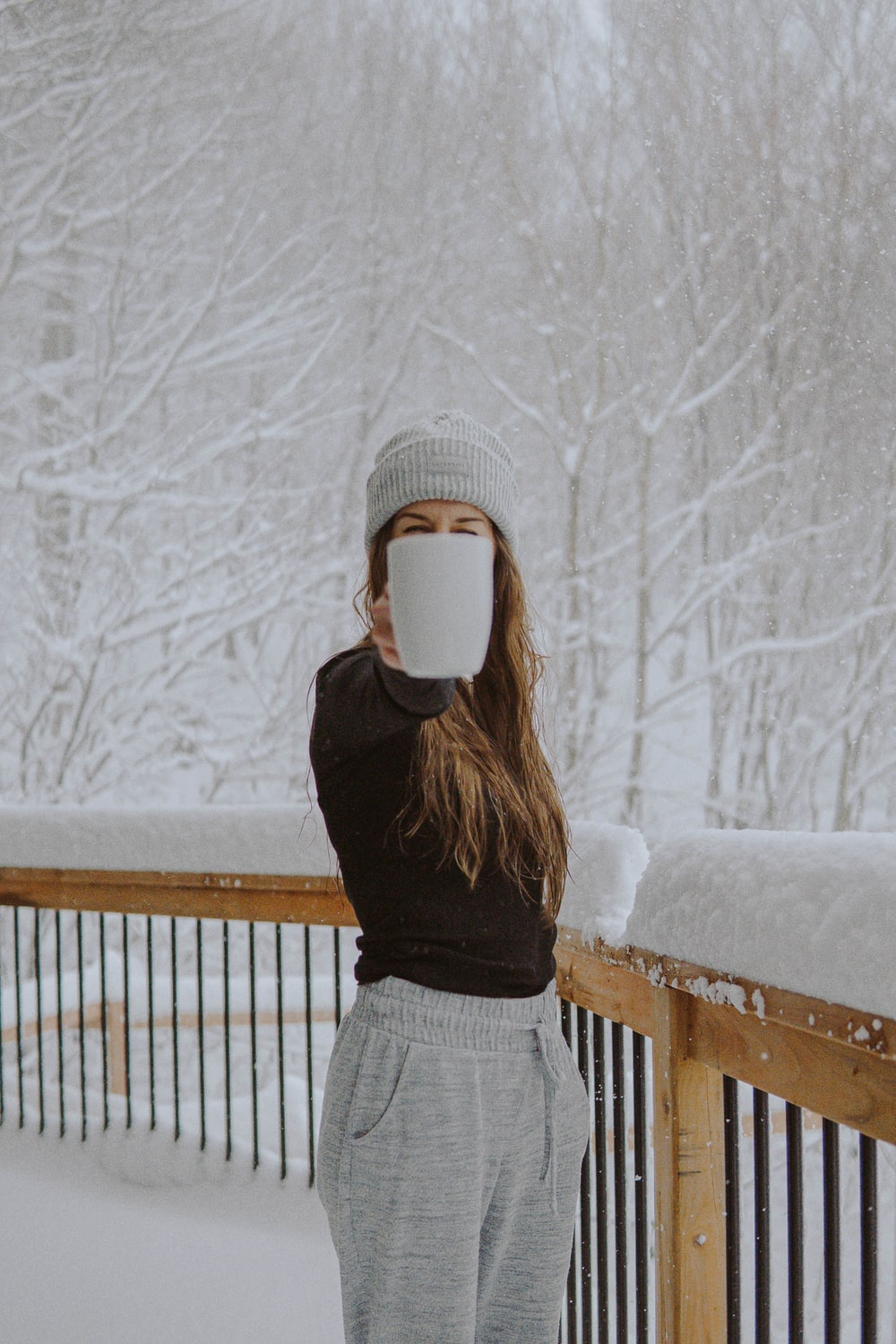 woman in black sweater and gray and white plaid skirt standing on snow covered ground during