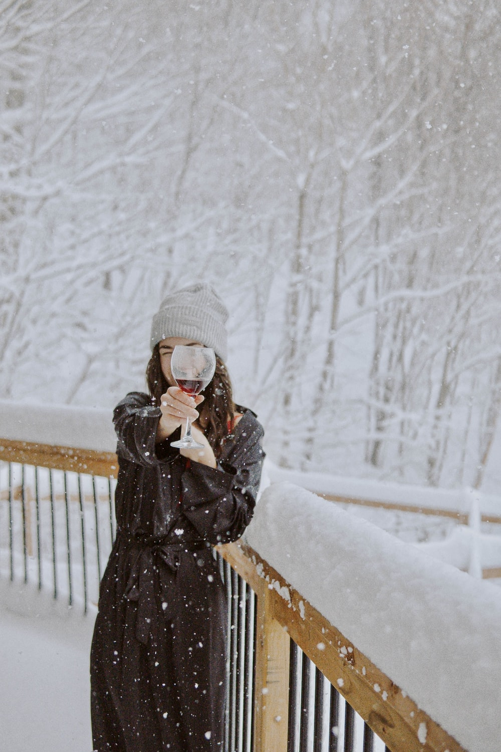 woman in black coat standing on snow covered ground during daytime