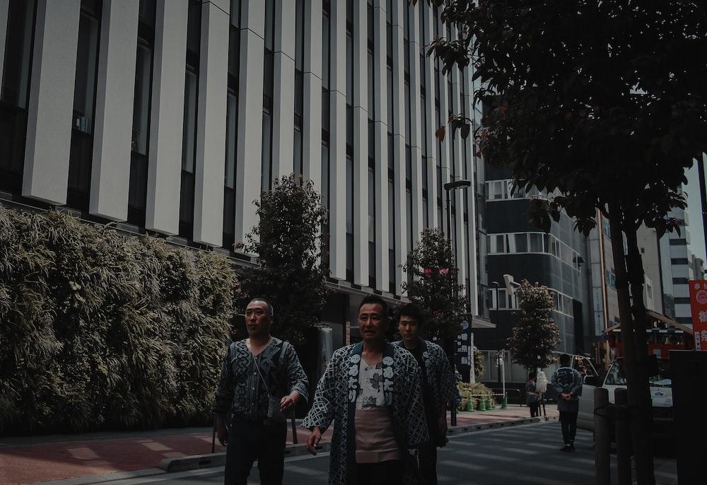 2 women standing near white building during daytime