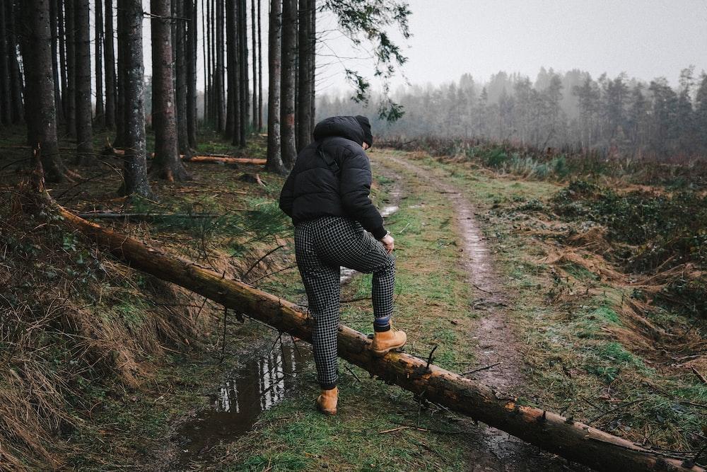 woman in black jacket and black pants walking on brown wooden log during daytime