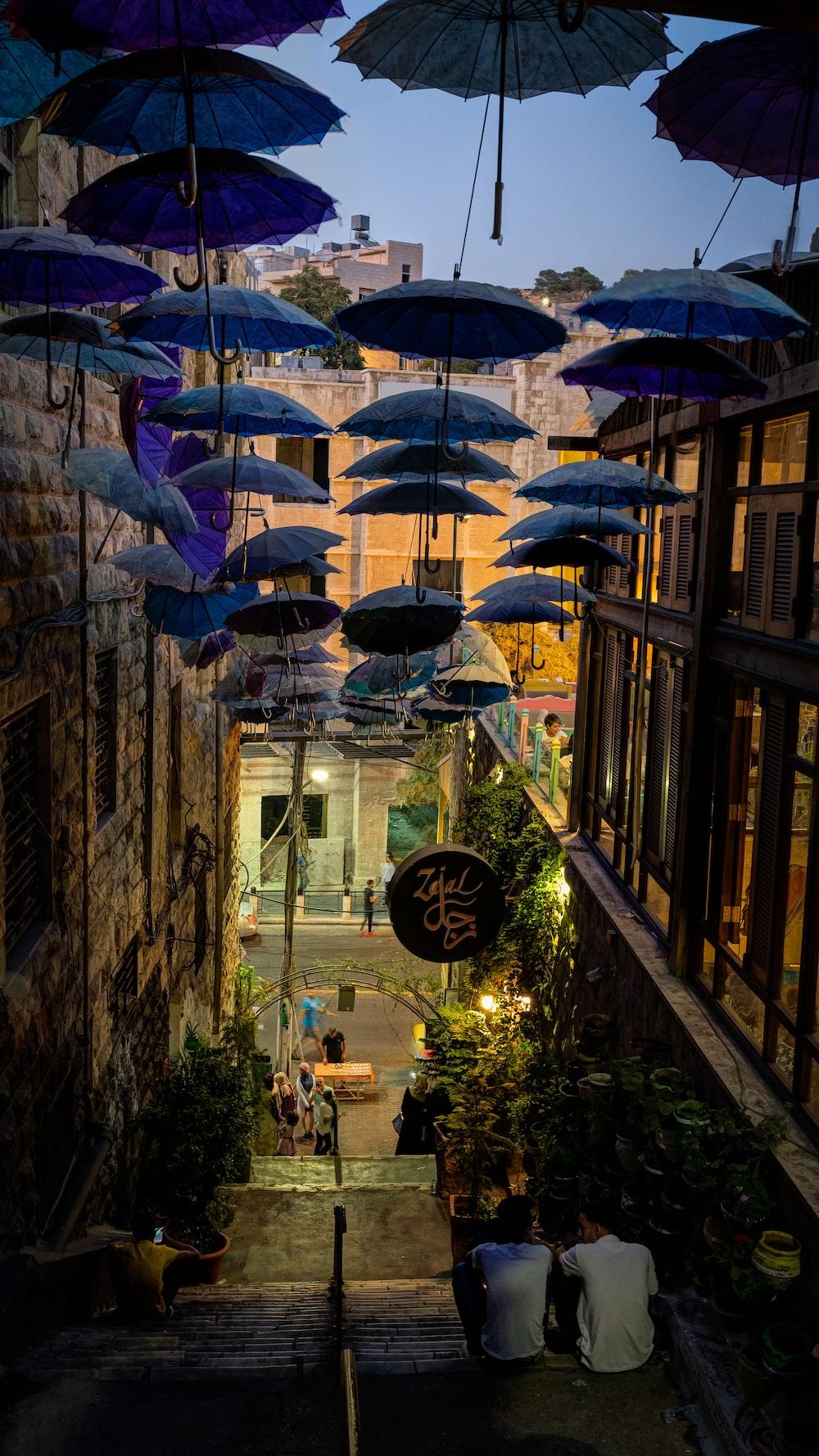 blue umbrella near brown brick building